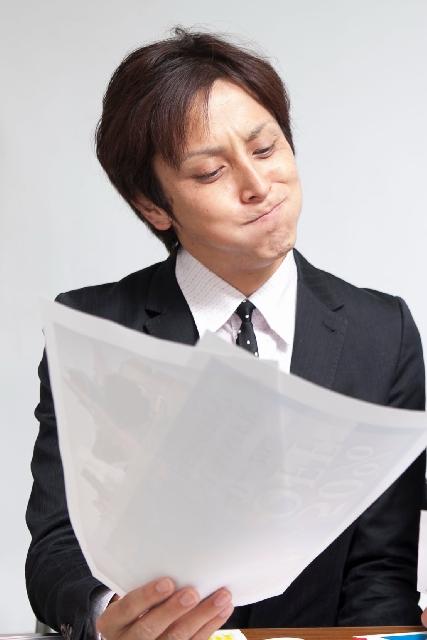 書類を見て悩む男性