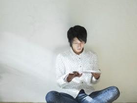 部屋で読書する男性