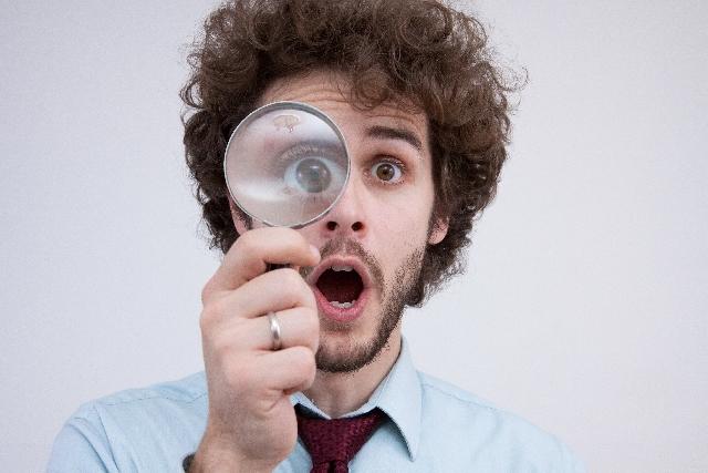 虫眼鏡を覗く外国人